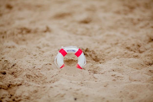 Cerca de salvavidas en miniatura cavar en la arena de la playa.