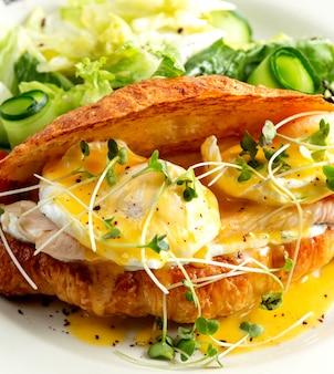 Cerca de sandwich de pollo con huevo benedict en croissant