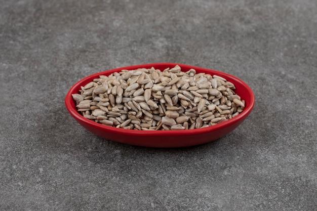 Cerca de semillas de girasol en recipiente rojo sobre superficie gris