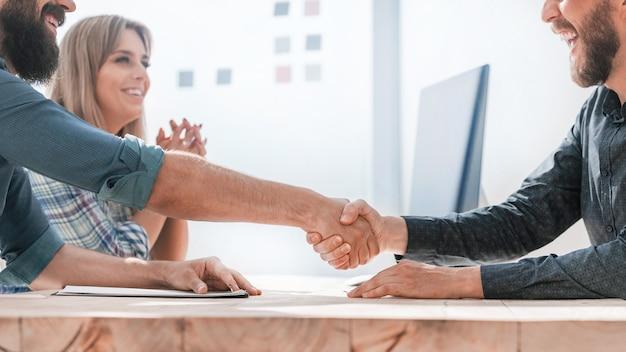 De cerca. socios comerciales sonrientes dándose la mano. concepto de asociación