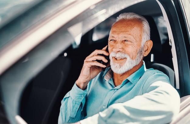Cerca de sonriente barbudo senior hablando por teléfono con el brazo en la ventana abierta mientras está sentado en el coche.