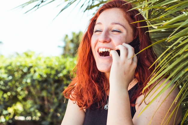 Cerca de sonriente chica atractiva con pelirroja hablando por teléfono móvil mientras está de pie al aire libre