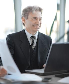 De cerca. sonriente, hombre de negocios mayor, sentado, en, el suyo, escritorio