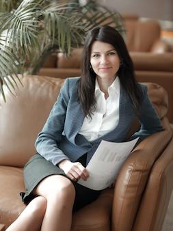 De cerca. sonriente, mujer de negocios, sentado, en, vestíbulo, de, oficina