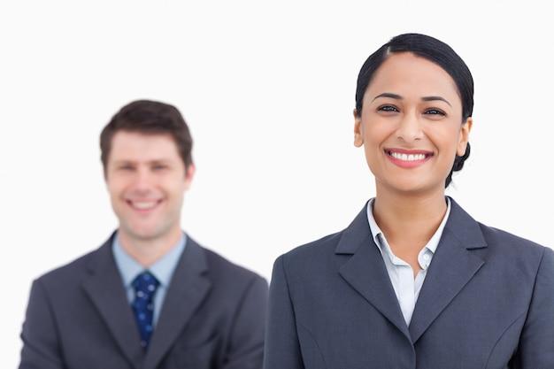 Cerca de sonriente vendedora con colega detrás de ella