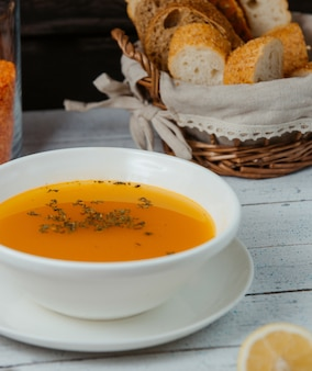 Cerca de sopa de lentejas en un tazón servido con pan