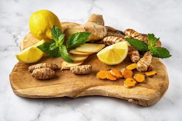 Cerca de la tabla de madera con jengibre, cúrcuma, limones y menta sobre una superficie blanca - ingredientes para el té que estimula el sistema inmunológico. concepto de comida de invierno