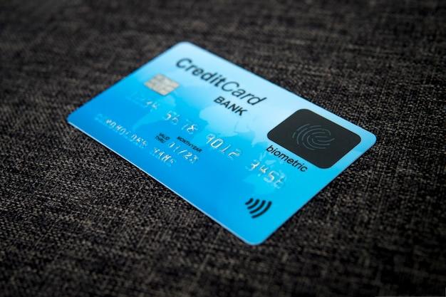 Cerca de la tarjeta de crédito con nueva tecnología de reconocimiento de huellas dactilares en el fondo material de tela de saco. tarjeta con chip electrónico, datos del titular de la tarjeta y signo biométrico en su anverso. biometría en banca.