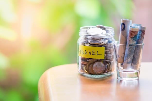 Cerca del tarro lleno de monedas y billetes en vidrio con carta de viaje