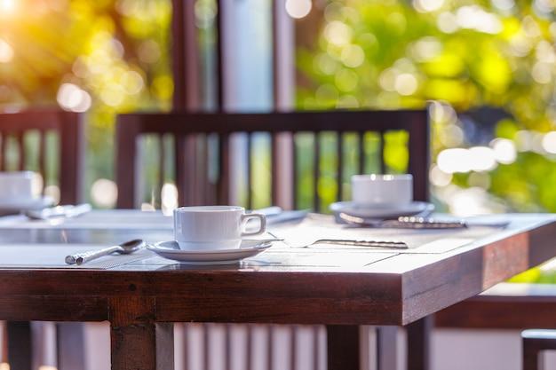 Cerca de la taza de café con leche en un piso de madera