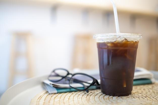 Cerca de la taza de plástico para llevar de café negro helado americano en mesa redonda