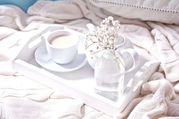 Cerca de la taza de té, leche, tetera y bouquet