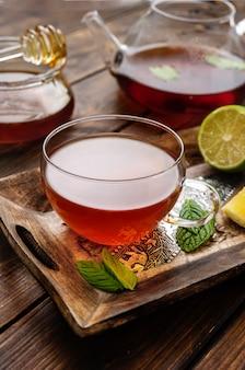 Cerca de la taza de té en la paleta de madera en estilo rústico