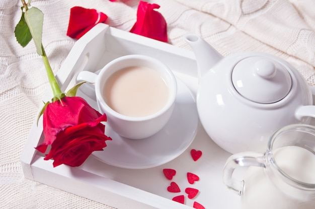 Cerca de la taza de té con rosa roja en la bandeja blanca