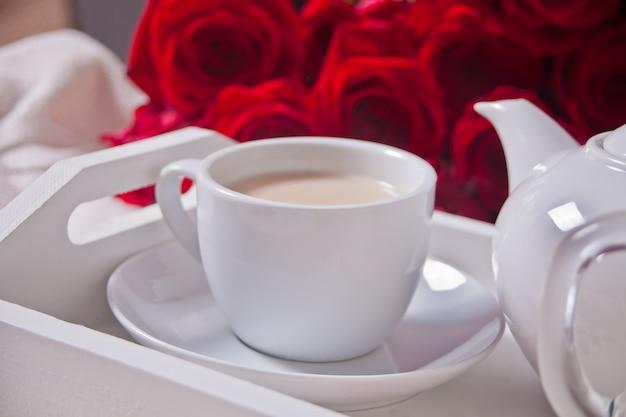Cerca de la taza de té con rosas rojas en la bandeja blanca