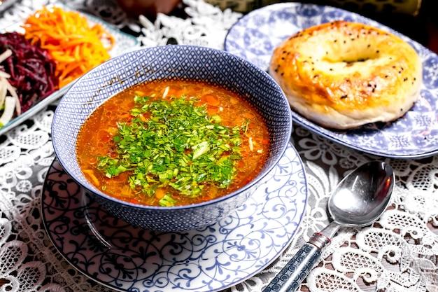Cerca del tazón de sopa de verduras adornado con hierbas