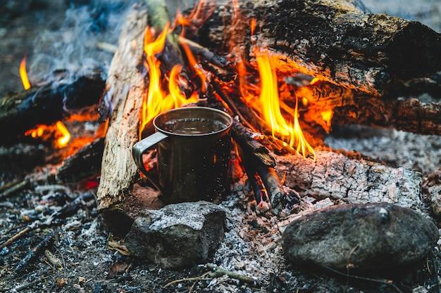 Cerca de té en taza de metal se calienta en hoguera