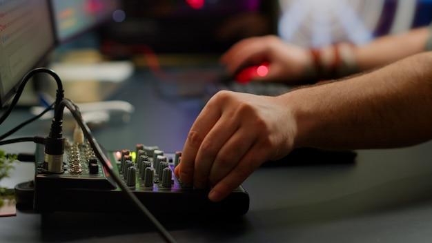 Cerca del teclado profesional con transmisión de iluminación rgb en el chat. jugador que usa una poderosa computadora para juegos en el estudio casero de un videojuego de deportes escribiendo en el teclado jugando un videojuego de disparos espaciales.