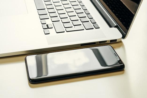Cerca del teléfono inteligente negro cerca del portátil abierto