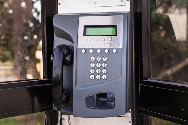 Cerca del teléfono público de pago en la calle