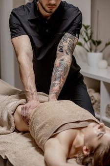 Cerca del terapeuta haciendo masaje de estómago a la mujer en el spa.