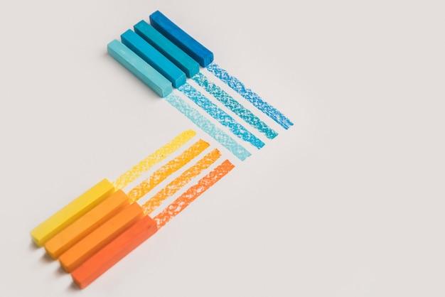 Cerca de tizas de crayón pastel de color sobre su propia línea de traza