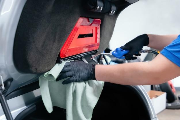 Cerca del trabajador de lavado de coches con guantes protectores y limpieza del maletero del coche con aire comprimido y una toallita