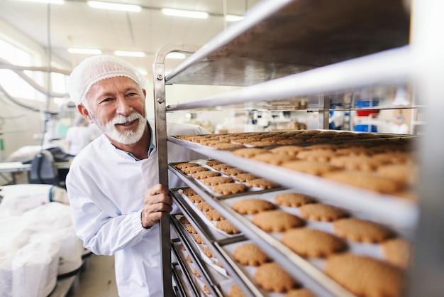 Cerca de trabajador senior en uniforme estéril empujando estante con galletas. interior de la fábrica de alimentos.