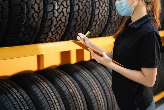 Cerca de la trabajadora usa una máscara para evitar la propagación del virus corona o covid-19, revisa el stock de neumáticos de automóvil en el almacén y escribe algunas notas.