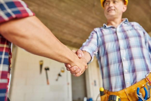 Cerca de trabajadores cooperando y estrechándose la mano
