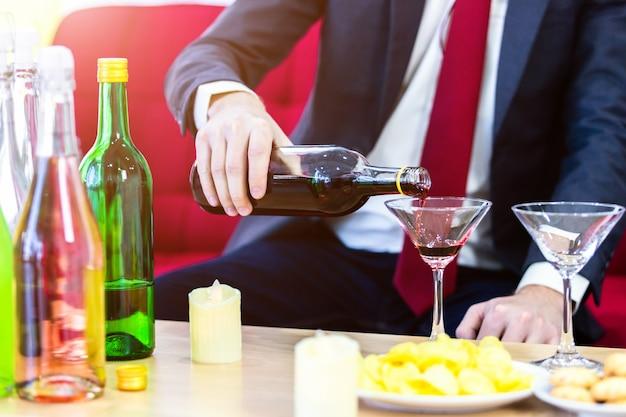 Cerca de un traje de negocios del hombre vertiendo champán en vaso