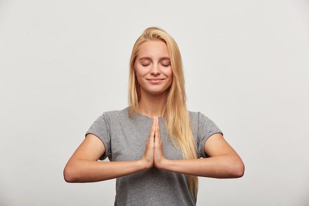 Cerca de la tranquila mujer rubia sonrisas, se concentra en algo agradable, practicando ejercicios de yoga de respiración