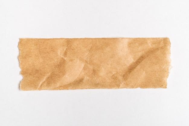 Cerca de un trozo de papel marrón rasgado sobre fondo blanco.