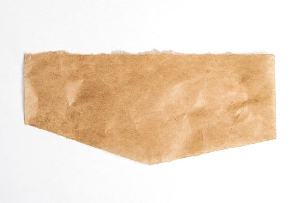 Cerca de un trozo de papel marrón rasgado sobre una superficie blanca