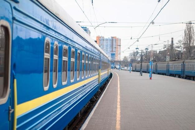Cerca del vagón de ferrocarril de metal azul con ventanas limpias de pie en la plataforma de la estación de tren. salida o llegada de un tren. concepto de viaje