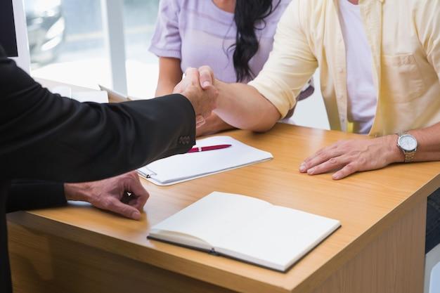 Cerca de vendedor agitando la mano de un cliente