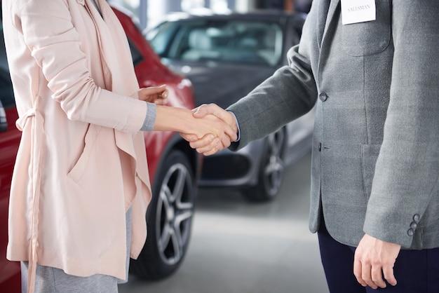 Cerca de vendedor y mujer de apretón de manos