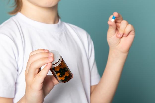 De cerca, ver niño lindo dulce adorable celebración pastillas en camiseta blanca sobre azul