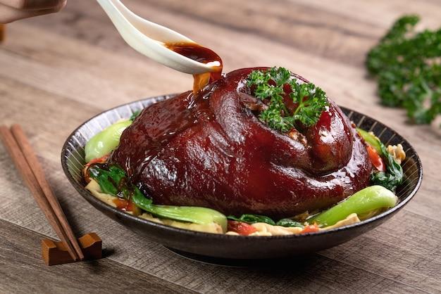 Cerca de verter la sabrosa salsa de soja con una cuchara sobre la comida taiwanesa estofado corvejón de cerdo en un plato sobre el fondo de la tabla rústica.