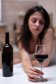Cerca de vidrio y botella llena de vino para mujer