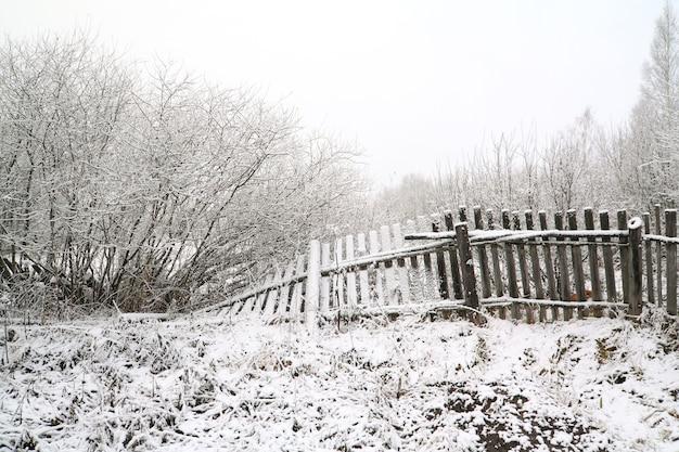 Cerca vieja cubierta de nieve en el paisaje de invierno