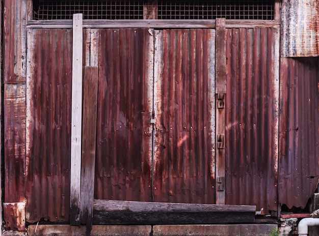 Cerca vieja envejecida vintage oxidada acanalada rojo marrón texturizada cerca de la lámina de metal de la aleación de la aleación del cinc usada en sector de la construcción como material de construcción de viviendas.