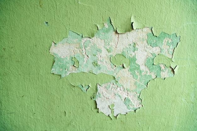 Cerca de viejas grietas de estuco en la pared, grietas de pintura desgastada en yeso.