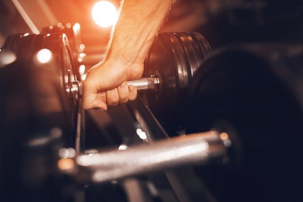 De cerca. vista de la mano escogiendo una pesa de metal.