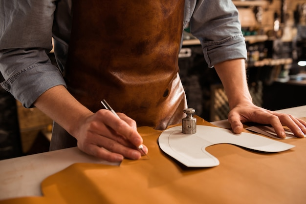 Cerca de un zapatero masculino corte textil de cuero