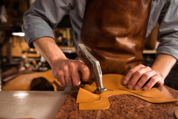 Cerca de un zapatero trabajando con cuero