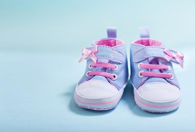 Cerca de zapatillas de bebé sobre fondo azul.