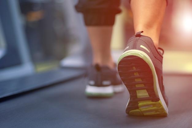 De cerca en el zapato, las mujeres que se ejecutan en un gimnasio en una caminadora haciendo ejercicio