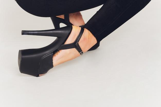 Cerca de zapatos con tacones altos en las piernas