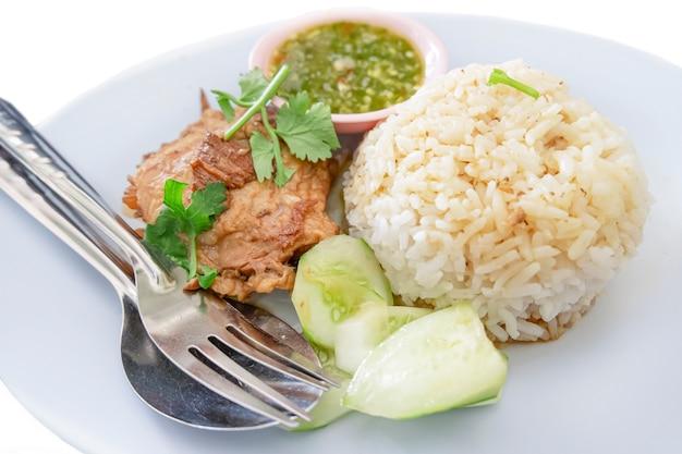 Cerdo asado con arroz y salsa aislado en blanco